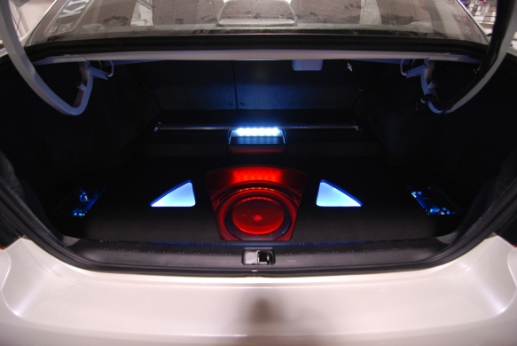 Strut tower visible with custom trunk setup. Plexi glass installed to protect subwoofer when cargo is in the trunk