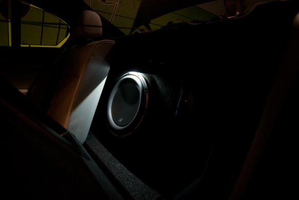 Subwoofer firing forward to avoid trunk rattle